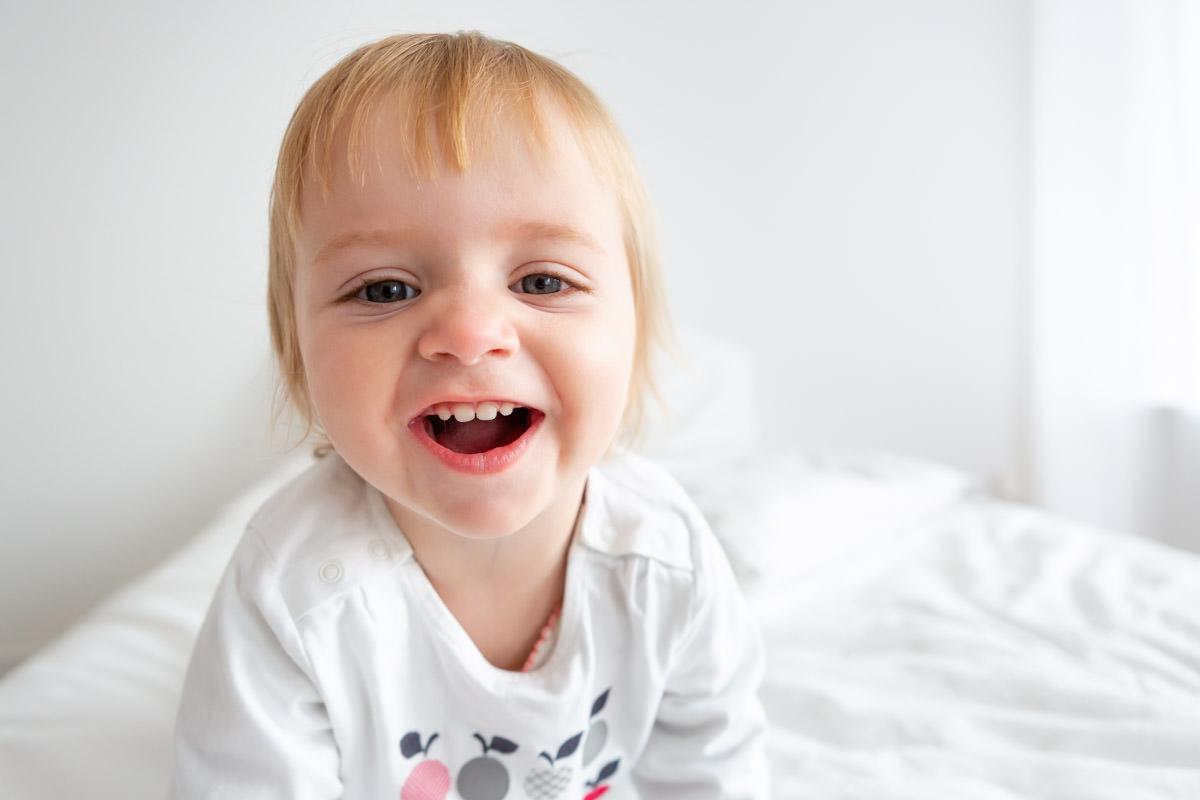 améliorer ses photos d'enfant : portrait de petite fille sur un lit