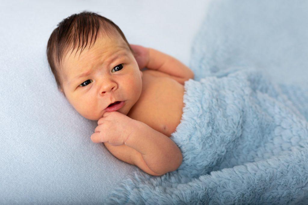 photographie d'un bébé garçon dans un décor bleu