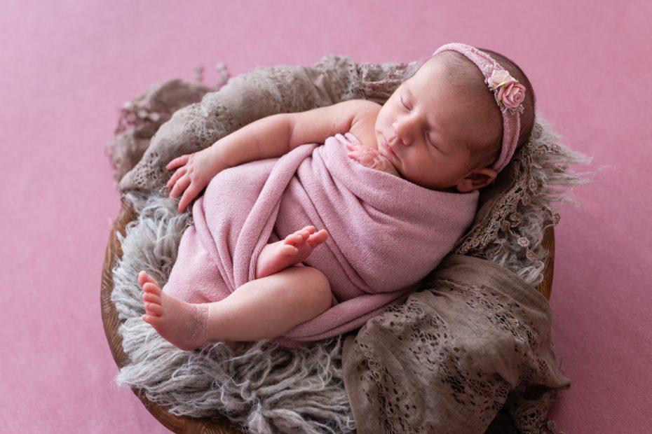 photo de nouveau-né fille dans un décor rose
